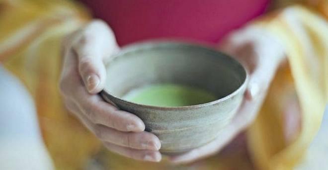 Японка несёт чашку с нефритовым напитком